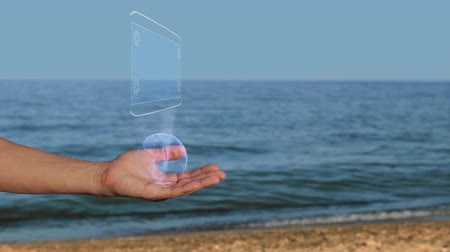 esquema : Male hands on the beach hold a conceptual hologram with the text Global Business. A man with a holographic technology on the background of the sea