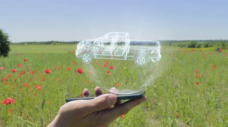 ピックアップ : Hologram of pickup truck on a smartphone. Person activates holographic image on the phone screen on the field with blooming poppies