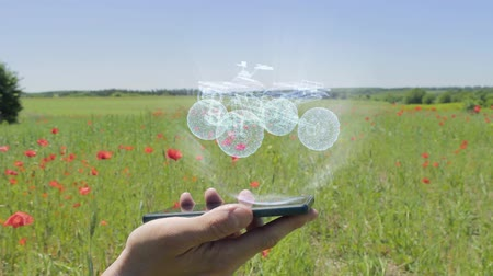 quad bike : Hologram of quad bike on a smartphone. Person activates holographic image on the phone screen on the field with blooming poppies