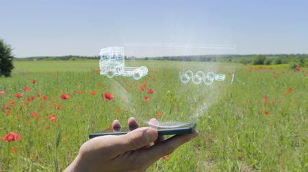 tir : Hologram of Truck on a smartphone. Person activates holographic image on the phone screen on the field with blooming poppies