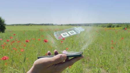 removable : Hologram of USB drive on a smartphone. Person activates holographic image on the phone screen on the field with blooming poppies