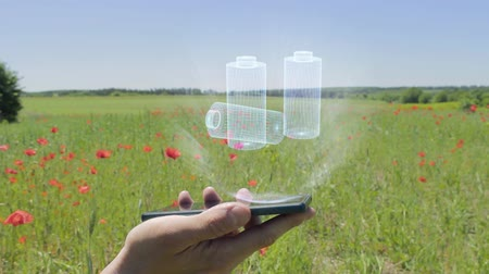 alkaline : Hologram of rechargeable batteries on a smartphone. Person activates holographic image on the phone screen on the field with blooming poppies