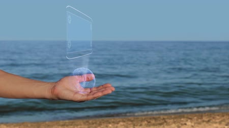 plano : Male hands on the beach hold a conceptual hologram with the text Startup. A man with a holographic technology on the background of the sea