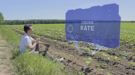 churn : Man is working on HUD holographic display with text Churn rate on the edge of the field. Businessman analyzes the situation on his plantation. Scientist examines future technology Stock Footage