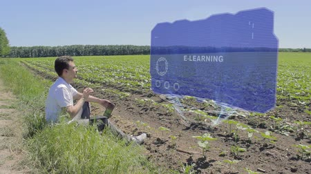 field study : Man is working on HUD holographic display with text E-learning on the edge of the field. Businessman analyzes the situation on his plantation. Scientist examines future technology Stock Footage