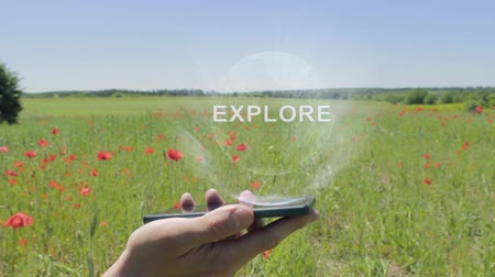 térképészet : Hologram of Explore on a smartphone. Person activates holographic image on the phone screen on the field with blooming poppies