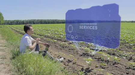 blízkost : Man is working on HUD holographic display with text Location-based services on the edge of the field. Businessman analyzes the situation on his plantation. Scientist examines future technology