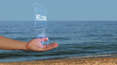 esquema : Male hands on the beach hold a conceptual hologram with the text Welcome. A man with a holographic technology on the background of the sea Stock Footage