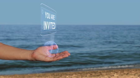 esclamativo : Male hands on the beach hold a conceptual hologram with the text You are invited. A man with a holographic technology on the background of the sea