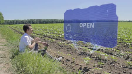 engedély : Man is working on HUD holographic display with text Open on the edge of the field. Businessman analyzes the situation on his plantation. Scientist examines future technology Stock mozgókép