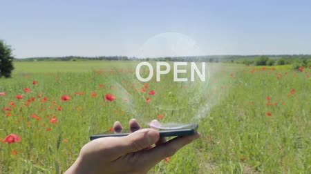 engedély : Hologram of Open on a smartphone. Person activates holographic image on the phone screen on the field with blooming poppies