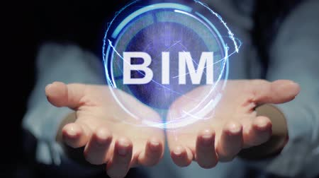 complexidade : Female hands show a round conceptual hologram with text BIM. Unrecognizable woman in ashen white on a black background with future holographic technology Vídeos