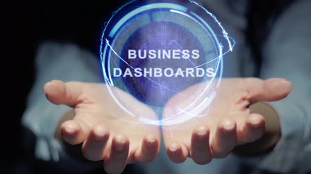 implementation : Female hands show a round conceptual hologram with text Business dashboards. Unrecognizable woman in ashen white on a black background with future holographic technology