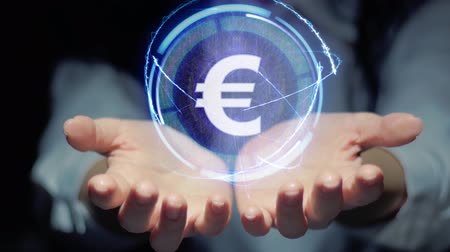 eur : Female hands show a round conceptual hologram with text Sign EUR. Unrecognizable woman in ashen white on a black background with future holographic technology