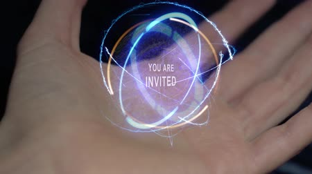восклицание : You are invited text in a round conceptual hologram on a female hand. Close-up of a hand on a black background with future holographic technology