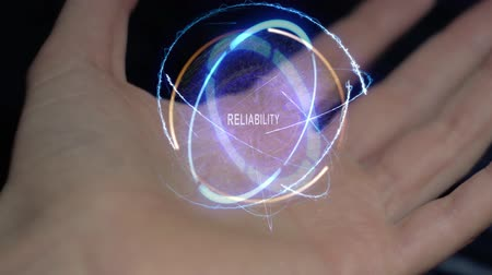 affidabile : Reliability text in a round conceptual hologram on a female hand. Close-up of a hand on a black background with future holographic technology Filmati Stock