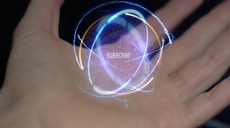 follower : Subscribe text in a round conceptual hologram on a female hand. Close-up of a hand on a black background with future holographic technology