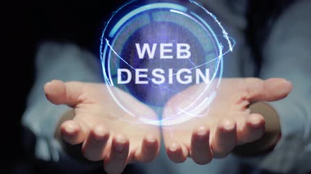 detection : Female hands show a round conceptual hologram with text Web Design. Unrecognizable woman in ashen white on a black background with future holographic technology Stock Footage