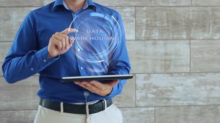 data cloud : Man activates a conceptual hologram with text Data Warehousing. The guy in the blue shirt and light trousers with a holographic screen gadget on the background of the wall Stock Footage