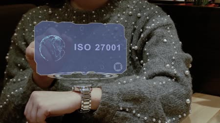 iso : Unrecognizable woman working with HUD hologram of a smart watch with text ISO 27001. Female hands with future holographic technology in wrist watches