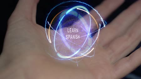 traduire : Learn Spanish text in a round conceptual hologram on a female hand. Close-up of a hand on a black background with future holographic technology