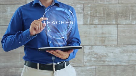 javul : Man activates a conceptual hologram with text Teacher. The guy in the blue shirt and light trousers with a holographic screen gadget on the background of the wall