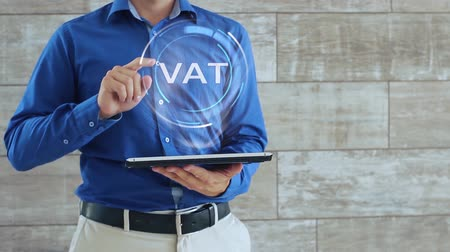 iva : Man activates a conceptual hologram with text VAT. The guy in the blue shirt and light trousers with a holographic screen gadget on the background of the wall Filmati Stock