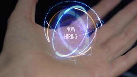 handen ineen : Now Hiring text in a round conceptual hologram on a female hand. Close-up of a hand on a black background with future holographic technology