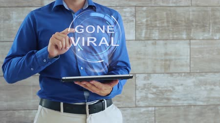 nesnel : Man activates a conceptual hologram with text Gone Viral. The guy in the blue shirt and light trousers with a holographic screen gadget on the background of the wall