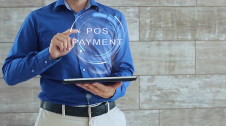 card pin : Man activates a conceptual hologram with text POS Payment. The guy in the blue shirt and light trousers with a holographic screen gadget on the background of the wall