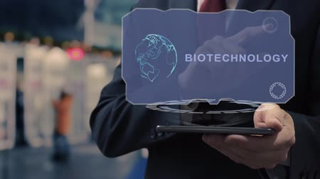 nanotechnologia : Unrecognizable businessman uses hologram on smartphone with text Biotechnology. Man in shirt and jacket with holographic screen on background of entrance to the airport or train station Wideo