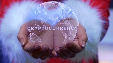 Female hands holding a conceptual hologram of planet Earth with text Cryptocurrency. Woman in red clothes with faux white fur with future holographic technology Stock Footage
