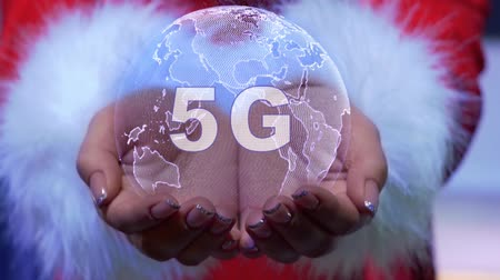 global business : Female hands holding a conceptual hologram of planet Earth with text 5G. Woman in red clothes with faux white fur with future holographic technology