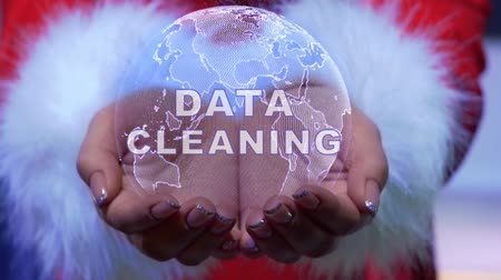 Female hands holding a conceptual hologram of planet Earth with text Data cleaning. Woman in red clothes with faux white fur with future holographic technology