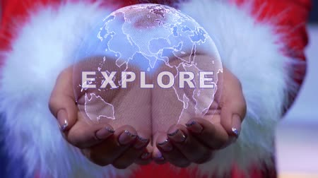 Female hands holding a conceptual hologram of planet Earth with text Explore. Woman in red clothes with faux white fur with future holographic technology Wideo