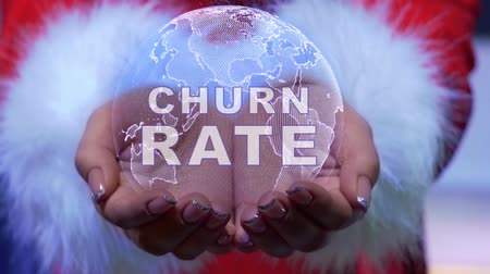 churn : Female hands holding a conceptual hologram of planet Earth with text Churn rate. Woman in red clothes with faux white fur with future holographic technology