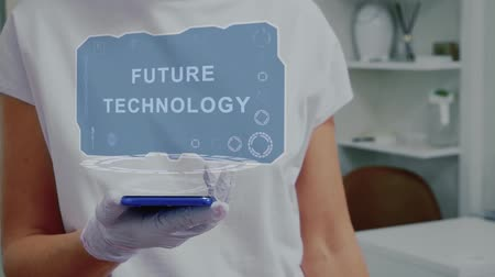 Doctor in medical glove against background of doctors office with HUD hologram text Future technology. Hand holds futuristic holographic gadget. Medical technology concept of the future
