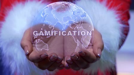 schemat : Female hands holding a conceptual hologram of planet Earth with text Gamification. Woman in red clothes with faux white fur with future holographic technology