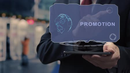 Unrecognizable businessman uses hologram on smartphone with text Promotion. Man in shirt and jacket with holographic screen on background of entrance to the airport or train station
