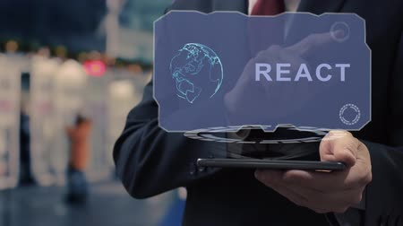 Unrecognizable businessman uses hologram on smartphone with text React. Man in shirt and jacket with holographic screen on background of entrance to the airport or train station
