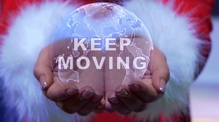 tutmak : Female hands holding a conceptual hologram of planet Earth with text Keep moving. Woman in red clothes with faux white fur with future holographic technology Stok Video