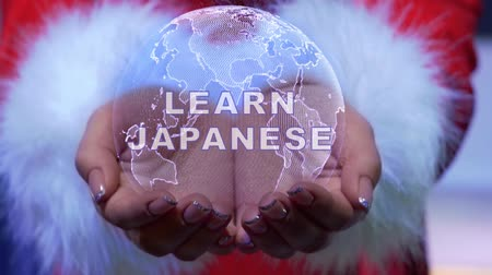 dialog : Female hands holding a conceptual hologram of planet Earth with text Learn Japanese. Woman in red clothes with faux white fur with future holographic technology