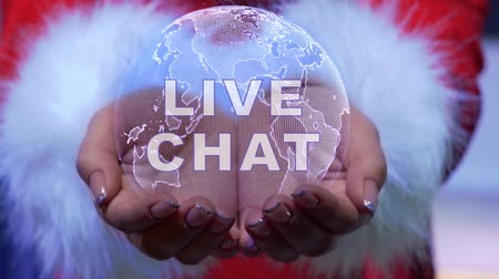 dialog : Female hands holding a conceptual hologram of planet Earth with text Live chat. Woman in red clothes with faux white fur with future holographic technology