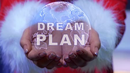 владелец : Female hands holding a conceptual hologram of planet Earth with text Dream plan. Woman in red clothes with faux white fur with future holographic technology