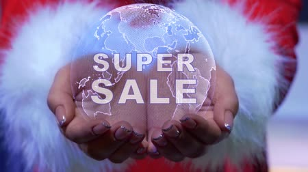 schemat : Female hands holding a conceptual hologram of planet Earth with text Super sale. Woman in red clothes with faux white fur with future holographic technology