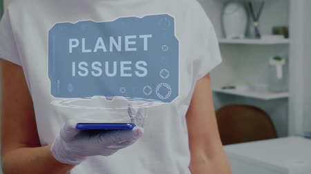 nuisible : Doctor in medical glove against background of doctors office with HUD hologram text Planet issues. Hand holds futuristic holographic gadget. Medical technology concept of the future Vidéos Libres De Droits