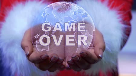 ortografia : Female hands holding a conceptual hologram of planet Earth with text Game Over. Woman in red clothes with faux white fur with future holographic technology