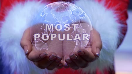 общаться : Female hands holding a conceptual hologram of planet Earth with text Most popular. Woman in red clothes with faux white fur with future holographic technology Стоковые видеозаписи