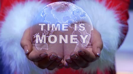 waluta : Female hands holding a conceptual hologram of planet Earth with text Time is money. Woman in red clothes with faux white fur with future holographic technology Wideo