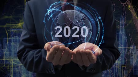 érintőképernyő : Male hands activate a conceptual holographic text 2020. Businessman in a suit with a hologram of planet Earth on a background of a futuristic wireframe city